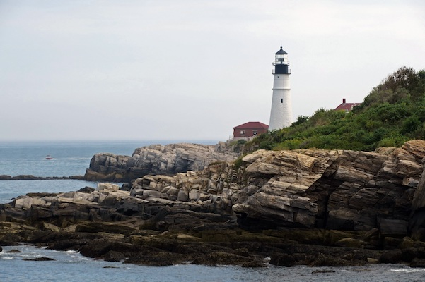a lighthouse perched on a rocky shore, under an overcast sky